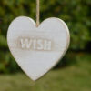 "wooden heart engraved with ""wish"" hanging from tree"