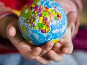child holding globe, raising globally conscious children