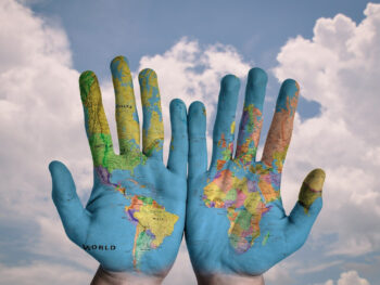 Open hands imprinted with world map