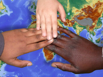 black, brown, and white hands on map, globally conscious children
